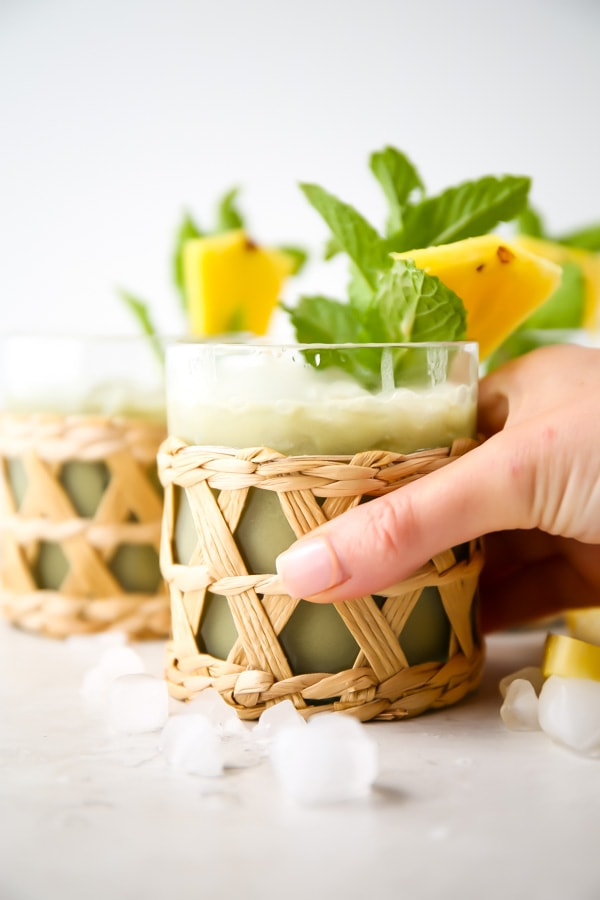 A hand is grabbing a glass of pineapple matcha drink.