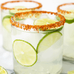 A glass of margarita has Tajin around the tim and is topped with ice and wedge of lime.