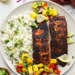 Blackened salmon is plated with coconut rice and mango salsa and topped with lemon wedges.
