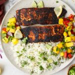 Blackened salmon is plated on a plate with coconut rice, and mango salsa.