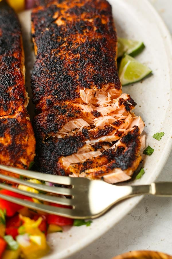 Salmon is flaked with a fork to show the tender, juicy texture.