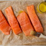 A brush slathers the salmon in melted butter ontop of parchment paper.
