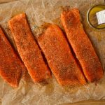 Salmon filets are plated on parchment paper and brushed with butter and blackening seasoning.