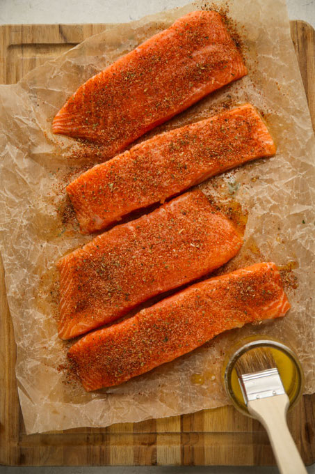 Salmon is placed on parchment paper and sprinkled with the blackening seasoning.