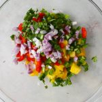 Mango salsa is made with red onion, cilantro, mango, and red pepper.