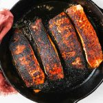 Salmon is pan seared in a hot cast iron until it is blackened.