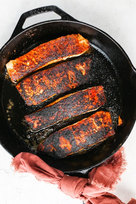 Blackened salmon is pan seared in a cast iron