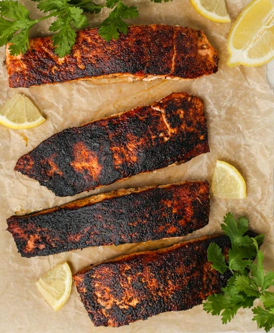 Blackened salmon is plated on parchment paper and topped with cilantro and lemon wedges.
