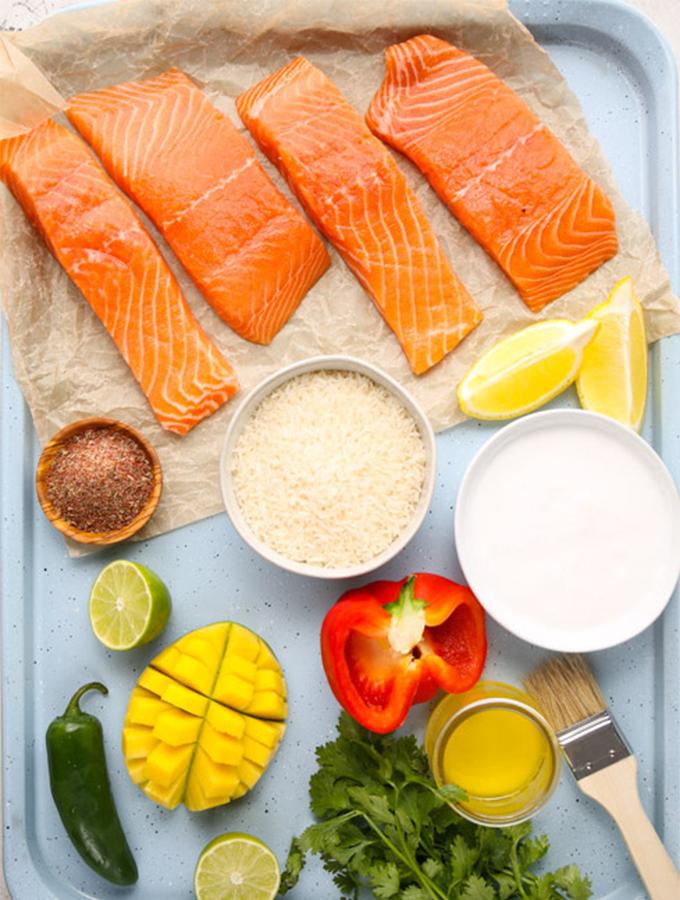 Salmon, rice, coconut milk, mango, and seasoning are displayed individually.