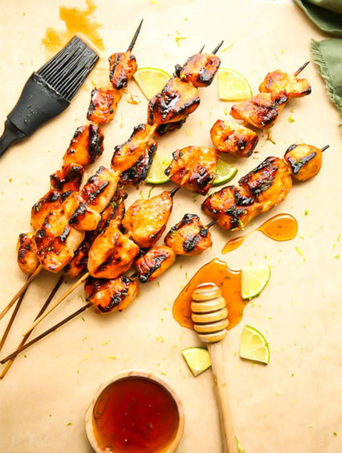 Grilled chicken kabobs are plated on parchment paper next to honey and lime wedges.