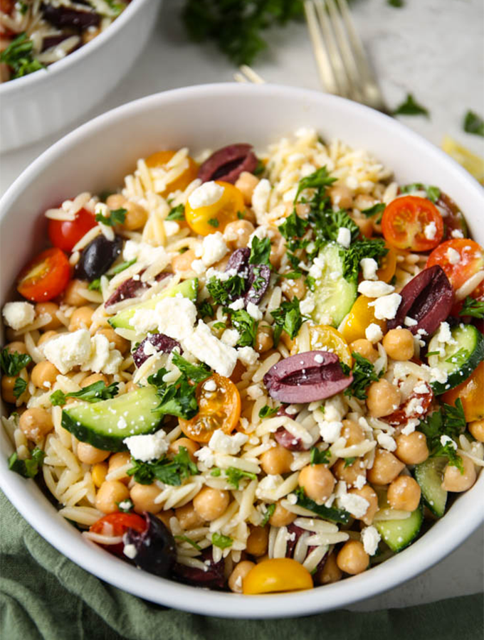 Orzo pasta salad is plated in a white bowl and topped with more feta cheese.