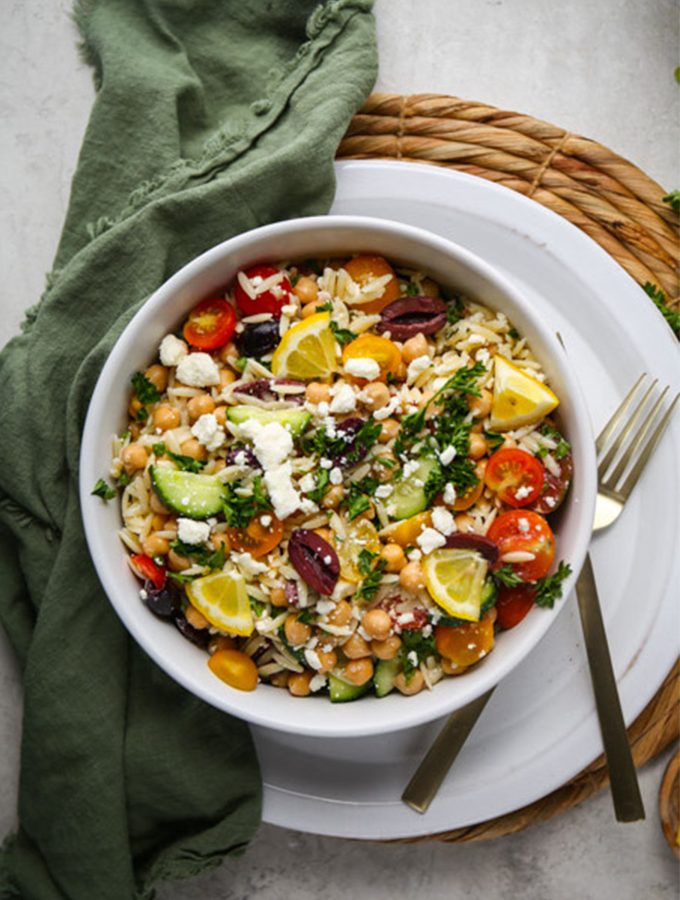 Orzo pasta salad is topped with more feta cheese and is plated in a small white bowl.