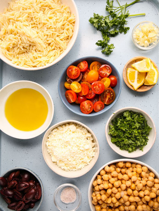 Greek orzo pasta salad ingredients are displayed individually in separate bowls.