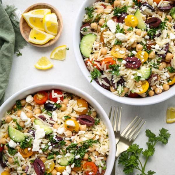 The orzo pasta salad is plated in two white bowls next to forks and lemon wedges.