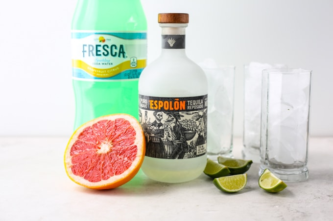 Tequila, grapefruit, soda, limes, and glasses of ice and placed individually.