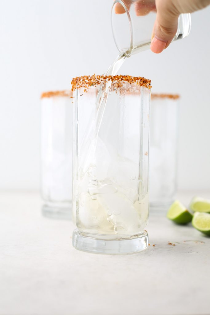 A hand is pouring tequila into a glass full of ice.