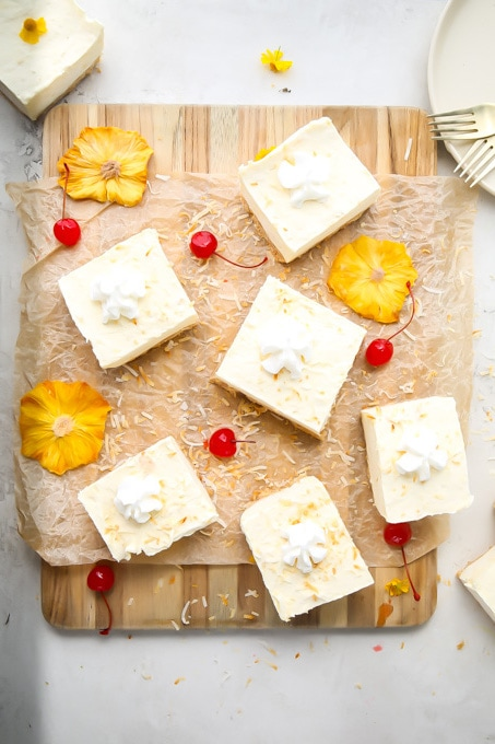 No bake cheesecake pina colada bars are sliced individually and placed next to flowers.