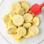 The sliced summer squash is tossed with the breadcrumbs, seasoning, and oil in a large bowl.