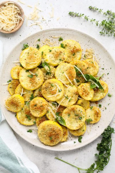 The summer squash is roasted, then plated on a white plate and topped with parsley.