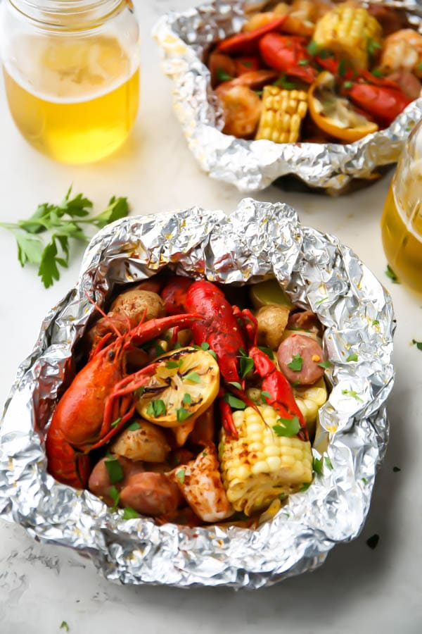 The shrimp foil packets are opened after cooking and topped with parsley and placed next to beer.