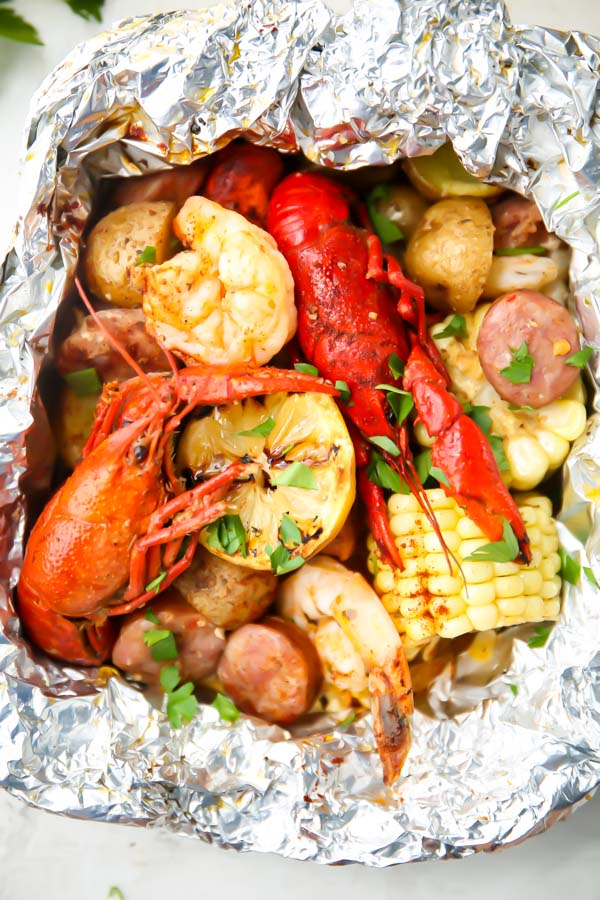 Crawfish, lemons, corn, potatoes, and sausage are cooked in a foil packet and topped with parsley.