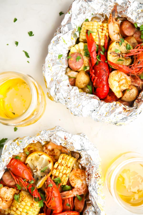 Shrimp, crawfish, corn, and potatoes are cooked in a foil packet and placed next to jars of beer.