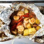 The shrimp foil packet is cooked and unwrapped and ready to eat.
