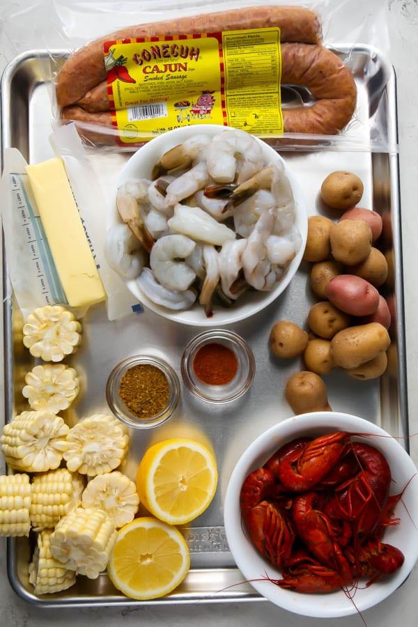 Shrimp, Cajun sausage, corn, lemons, butter, potatoes, and spices are displayed individually.