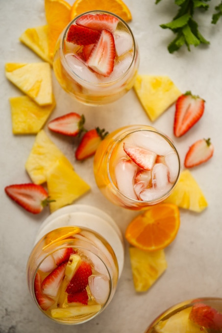 Three wine glasses are filled with glass and sangria and topped with fruit.
