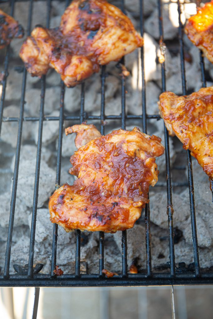 Chicken thighs are brushed with BBQ sauce while they are cooking on the grill.