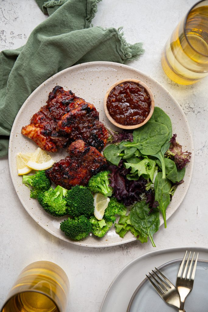 Chicken thighs are plated on a large plate with lemons, broccoli, and salad.