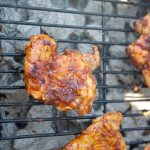 The chicken thighs are placed on the grilled and layered in BBQ sauce.