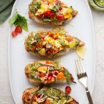 Chicken breasts are topped with pesto and a tomato basil mixture and plated on a white plate.