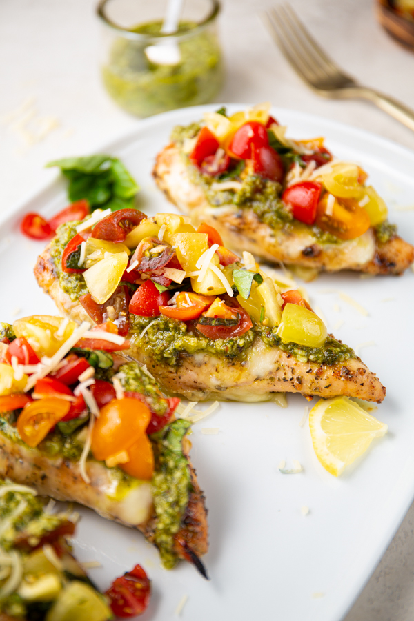Chicken breasts are topped with melted cheese, pesto, and a tomato basil mixture.