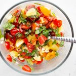 Tomatoes, basil, olive oil, and garlic are combined in a small bowl using a spoon.
