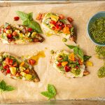 Chicken breasts are topped with pesto sauce and the tomato mixture.