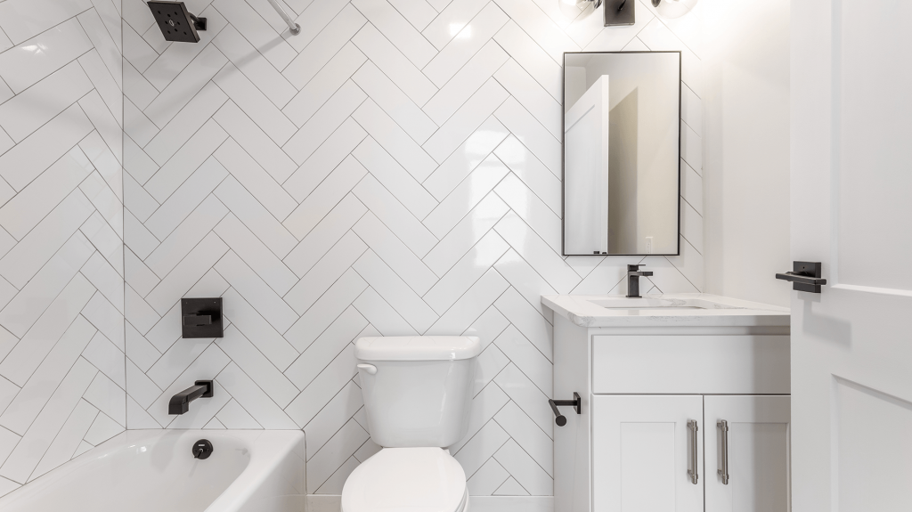 The bathroom boasts floor to ceiling tile with white cabinets and a marble sink.