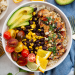 Rice, black beans, corn, tomatoes, avocado, and mojo chicken is added to a bowl to make a mojo chicken and rice bowl.