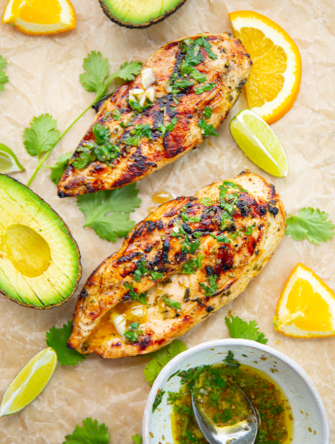 The chicken is grilled, then placed on parchment paper and drizzled with mojo marinade.