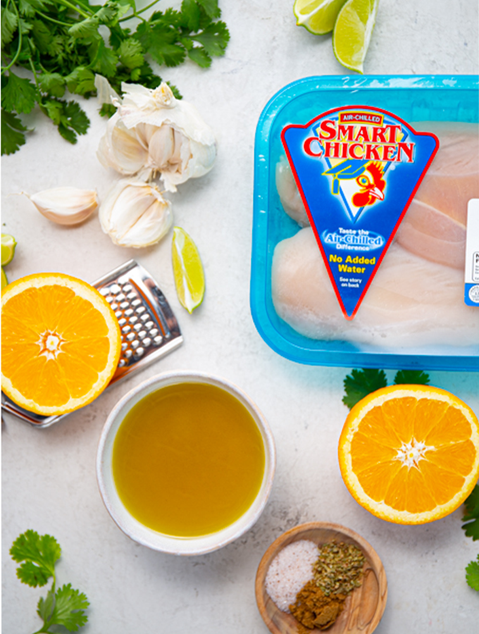 Mojo chicken ingredients are displayed individually and consists of seasoning, chicken, citrus, garlic, and cilantro.