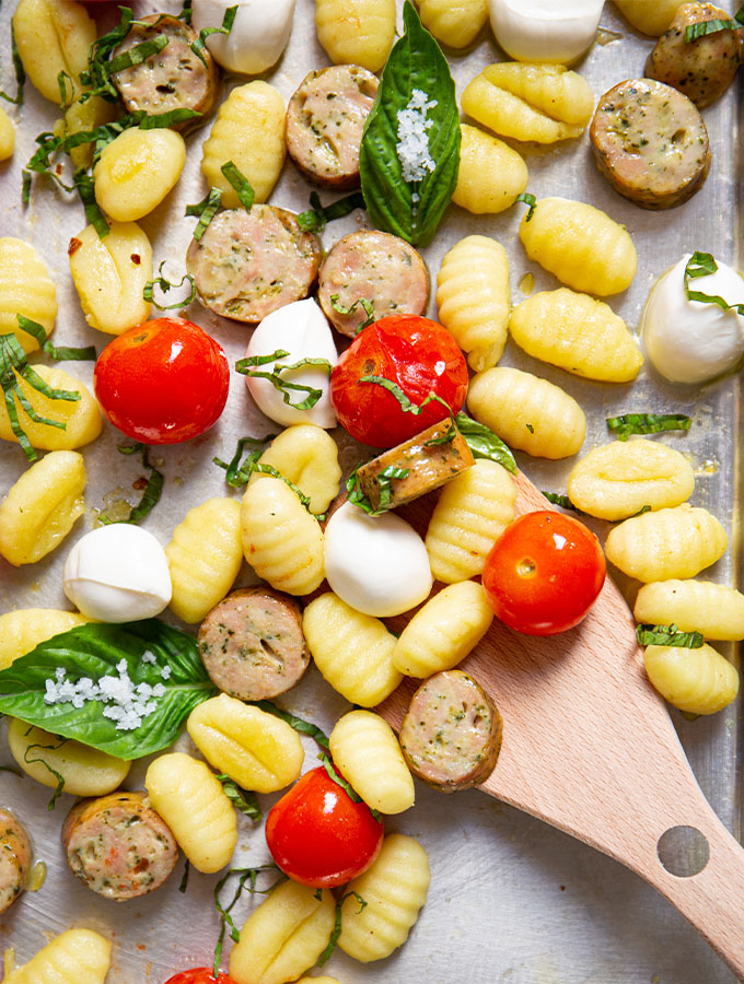 A spoon is scooping the gnocchi sheet pan mixture, which is topped with fresh basil.