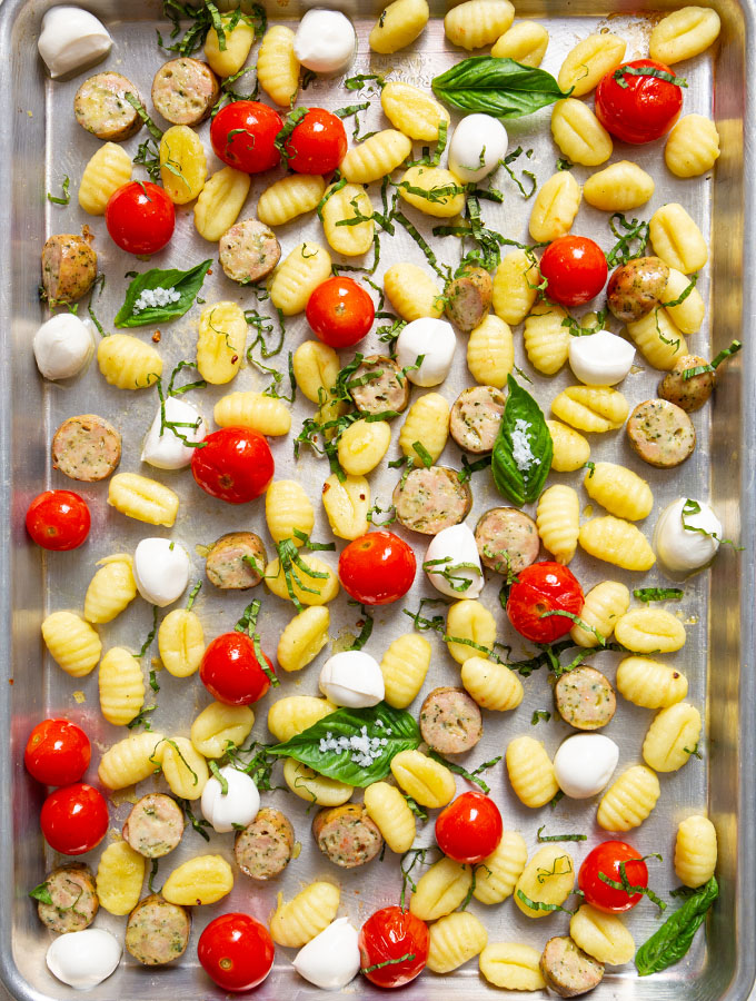 The gnocchi, tomatoes, and sausage is roasted on a sheet pan, then topped with fresh basil.