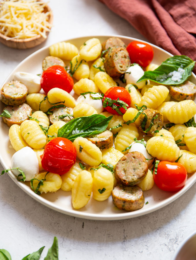 Blistered tomatoes, gnocchi, sausage, mozzarella, and basil are plated on a small plate.